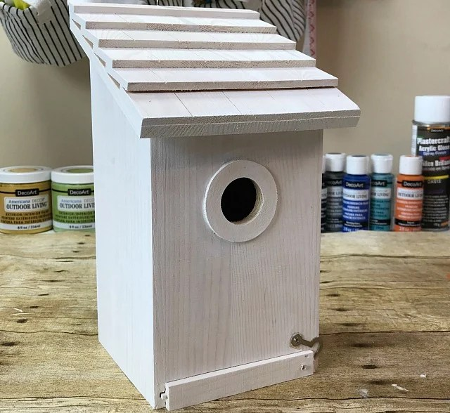 Step 1. Prime the birdhouse. Painting Birdhouses is a fun and easy birdhouse craft for any time of the year. We have painted a whole collection of decorative birdhouses for a new fence shelf in our backyard to invite more birds to stop by. You will find several here along with the stencil and paint colors we are using for our outdoor decor. #birding #birdhouse