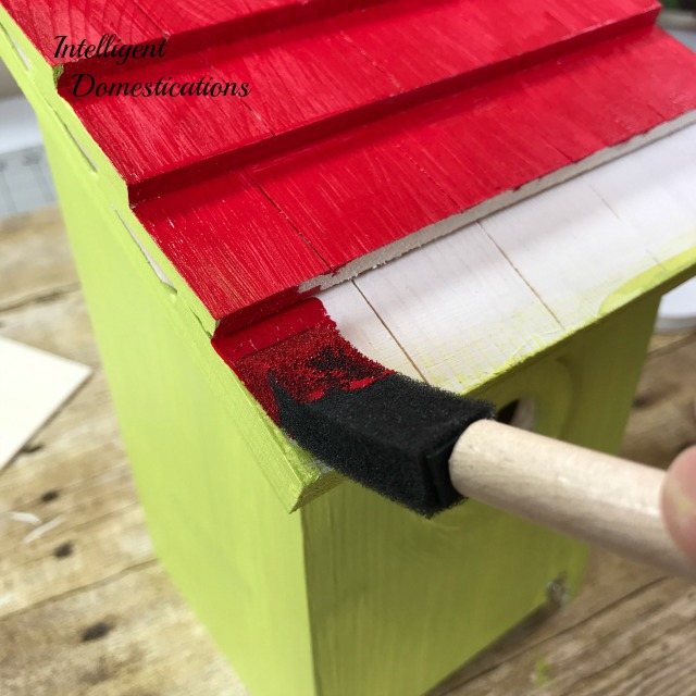 Step 2. Begin painting the outside of the birdhouse. Painting Birdhouses is a fun and easy birdhouse craft for any time of the year. We have painted a whole collection of decorative birdhouses for a new fence shelf in our backyard to invite more birds to stop by. You will find several here along with the stencil and paint colors we are using for our outdoor decor. #birding #birdhouse