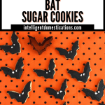 Bat shaped cookies decorated in black icing with white eyes on an orange and black polka dot cloth