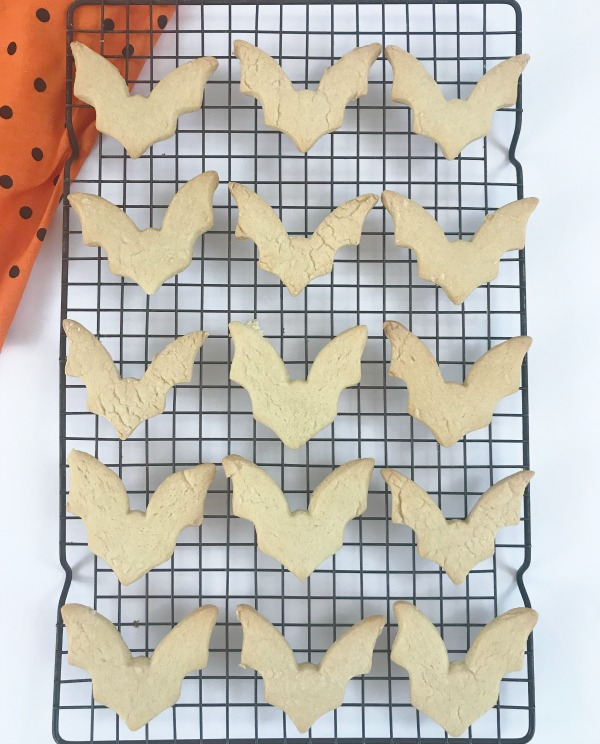Cookies cut into the shape of Bats on a cooling rack