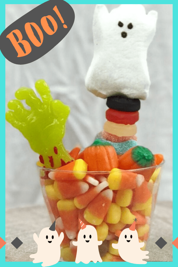 Halloween party favors. A cup of candy corn with Halloween candy kabobs sticking out