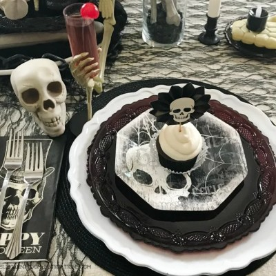 Halloween Skeleton Tablescape colors in white, cream and black. This Slightly spooky Halloween table decor is easy to replicate.