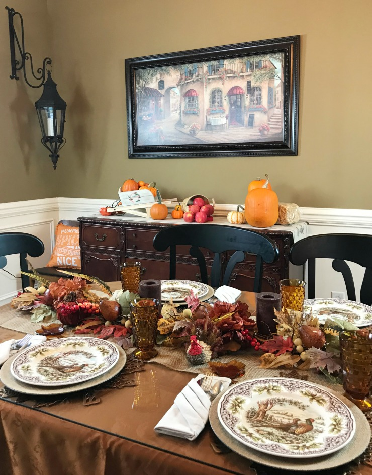 A Thanksgiving decorated Dining table with a view of the decorated buffet