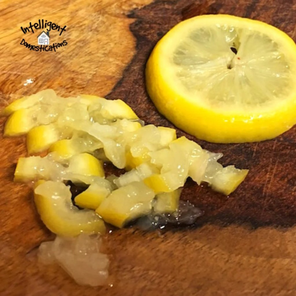 Lemon slice chopped up next to a lemon slice laying on a wooden chopping block