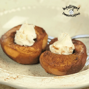 Baked peaches in a white bowl topped with whipped cream and sprinkled with cinnamon