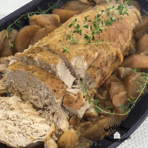 Baked Pork Tenderloin surrounded with baked apples and covered with Thyme in a casserole dish