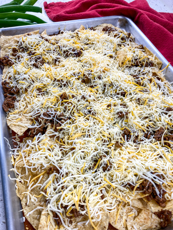Shredded cheese spread on top of meaty nachos