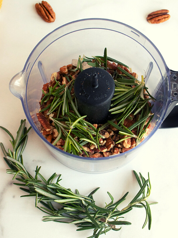 Pecans and fresh rosemary in a small food chopper