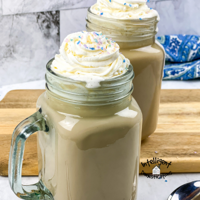 two mocha latte beverages served in Mason jars with whipped cream on top