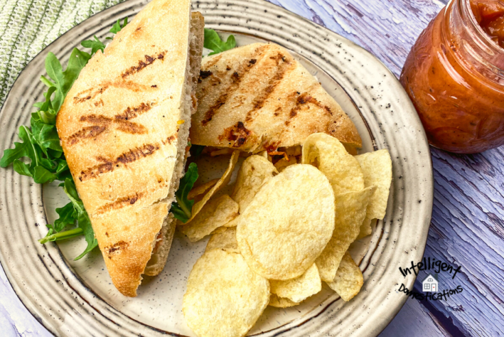 Panini cut in half with potato chips on a white plate and a jar of Peach sauce on a wooden table