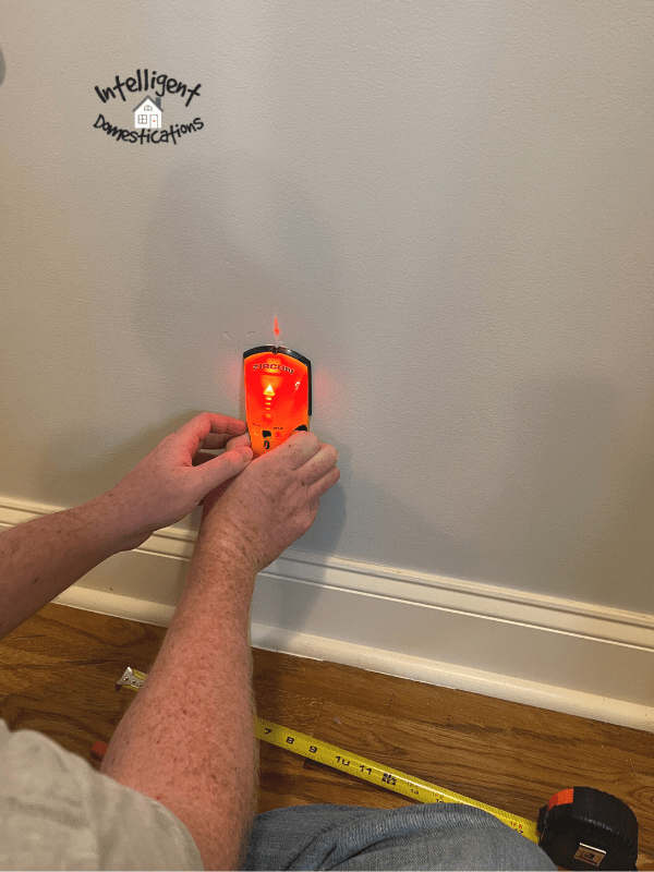 using a stud finder on a wall