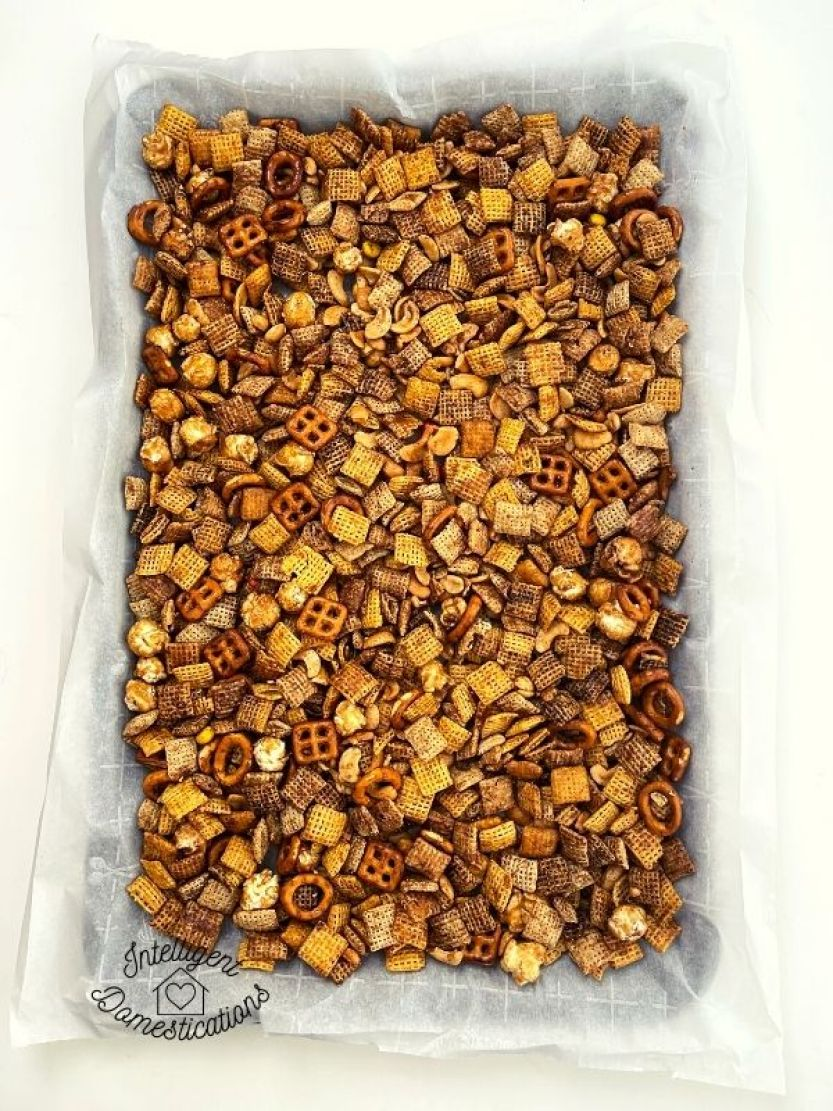 Pumpkin spice Chex mix on baking pan with parchment paper