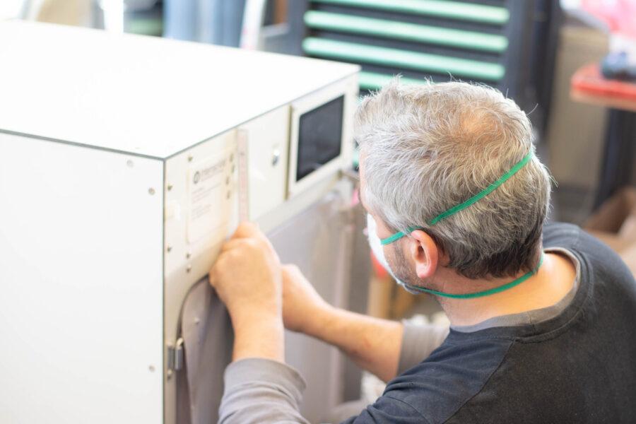 Intensovet Service Mitarbeiter beim Bekleben einer IntensoBox mit dem Firmenlogo.