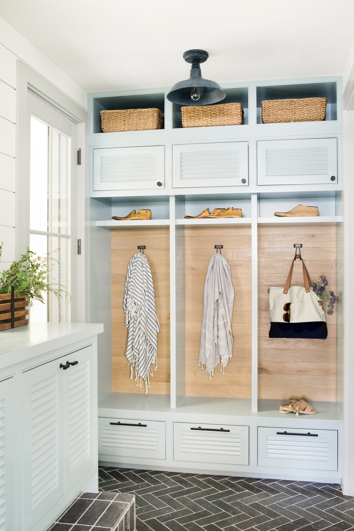 mudroom with white cubbies, white cabinetry, oak, herringbone tile, wood and natural textures