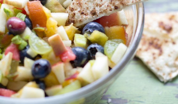 image of a bowl of creamy fruit salsa by intentionally eat with cindy newland, a cinnamon crisp chip is on the edge of the bowl