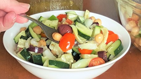 image of tangy greek chickpea salad full of cucumbers, onions, tomatoes, olives and peppers in a white bowl. A hand holding a forkful of salad on the side of the picture.