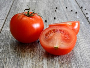 image of two tomatoes; one whole and one sliced in half with peppercorns in the background for the best gazpacho by intentionally eat
