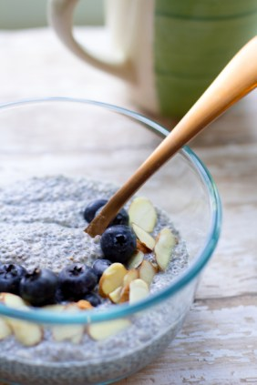 image of easy chia seed pudding by intentionally eat with blueberries, slivered almonds and a spoon