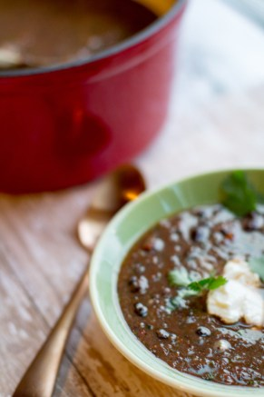 image of black bean soup quick and easy by intentionally eat in a green bowl with a copper spoon and red soup pot next to it