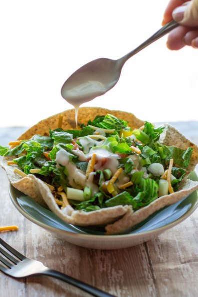 image of Quick and Healthy Taco Salad by Intentionally Eat with Cindy Newland with a spoon dripping dairy free sour cream