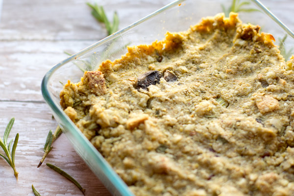 image of the tastiest vegan stuffing by intentionally eat with cindy newland in a glass dish surrounded by rosemary
