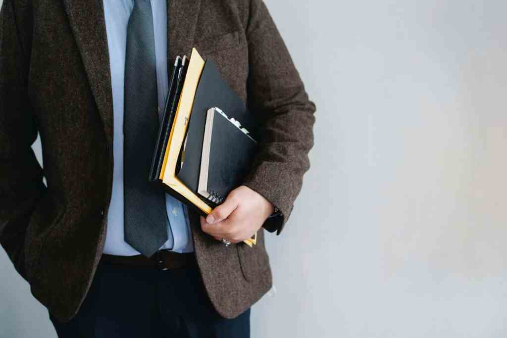 man in jacket holding books