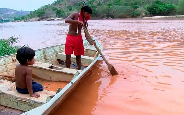 Members of Krenak people, father and son navigate on the turbid waters, completely contaminated, of the river Doce. Photo: Reproduction.