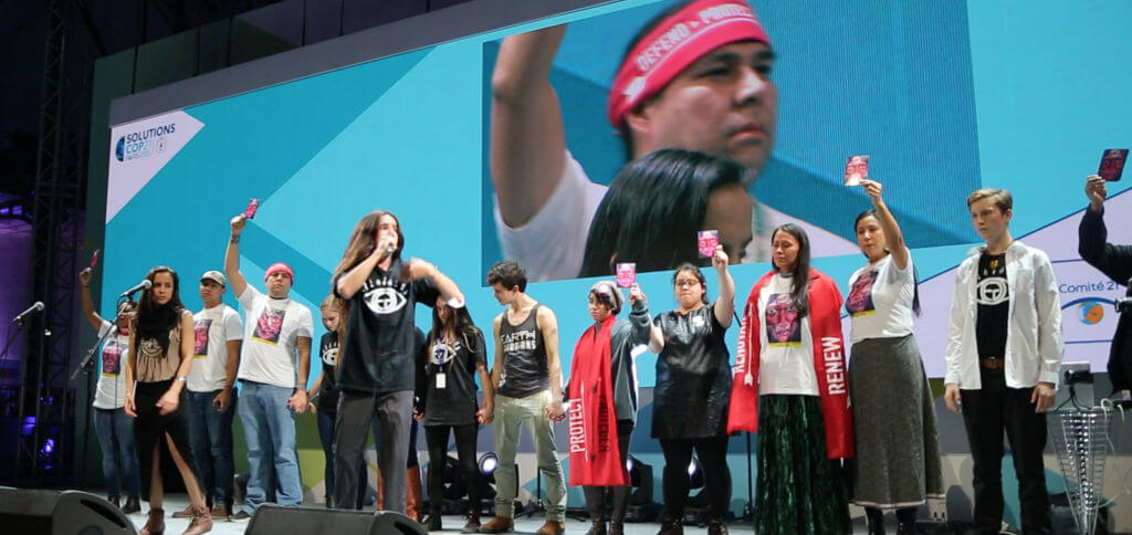 Indigenous activists protest at the COP21 Solutions Concert. Image via indigenousrising.org