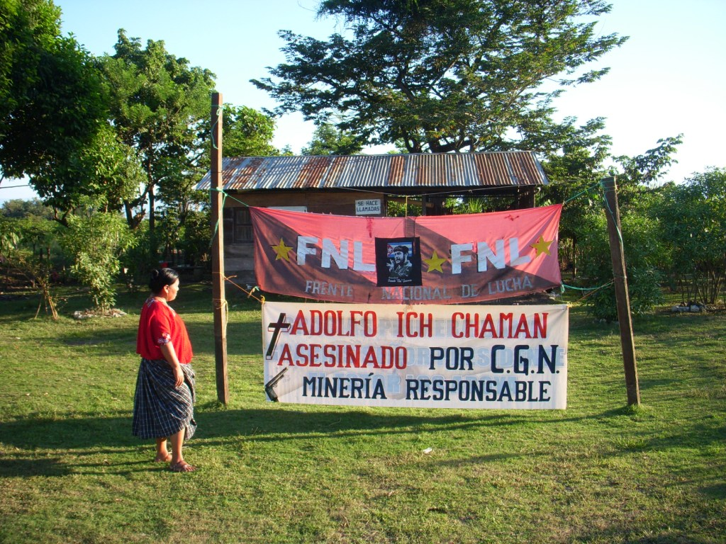 """Angelica Choc stands next to a sign that says """"Adolfo Ich murdered by CGN. Mining is responsible.""""  Photograph by Daniel Sosa via chocversushudbay.com"""
