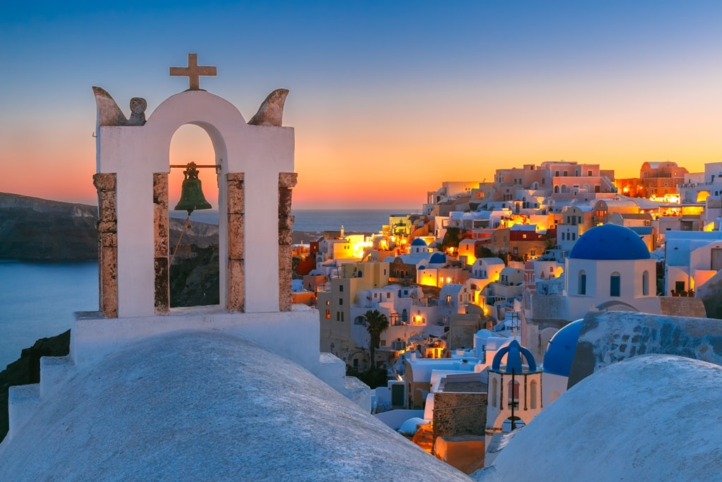 Arch-with-a-bell-white-houses-and-church-with-blue-domes-in-Oia-or-Ia-at-sunset-island-Santorini-Greece-min