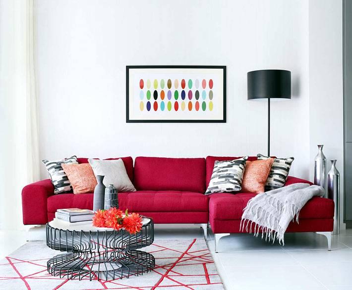 ярко-красный диван в дизайне интерьера гостиной комнаты