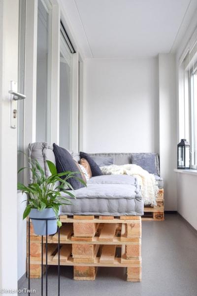 zitje van pallets en grijze loungekussens in serre