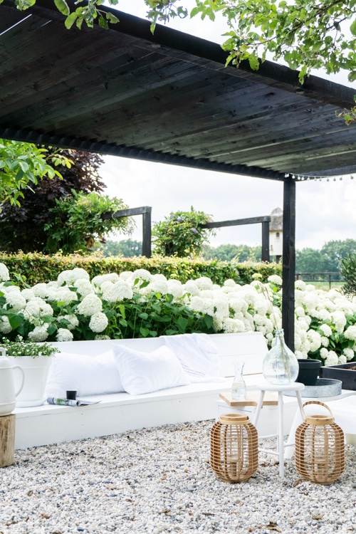 overkapping met loungebank en hortensia's binnen bij buitenhuis