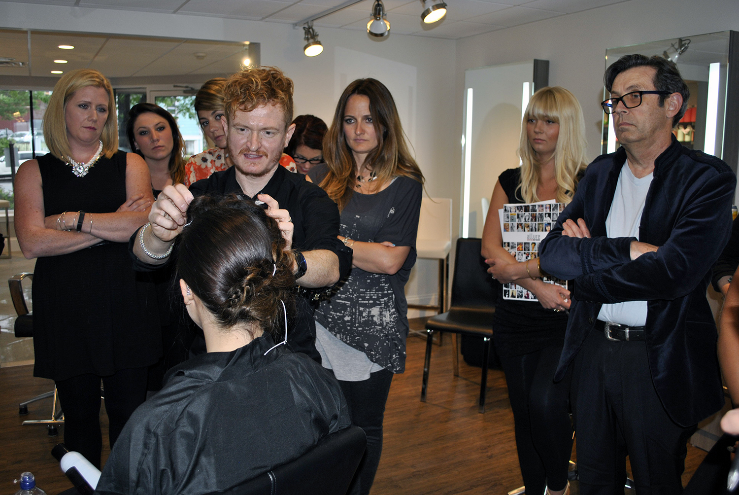 stylists gather around Travis to learn red carpet styling techniques at Shu Uemura education event