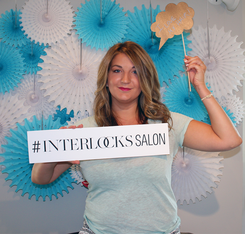 client in photo booth during INTERLOCKS Effortless Summer hair and makeup event