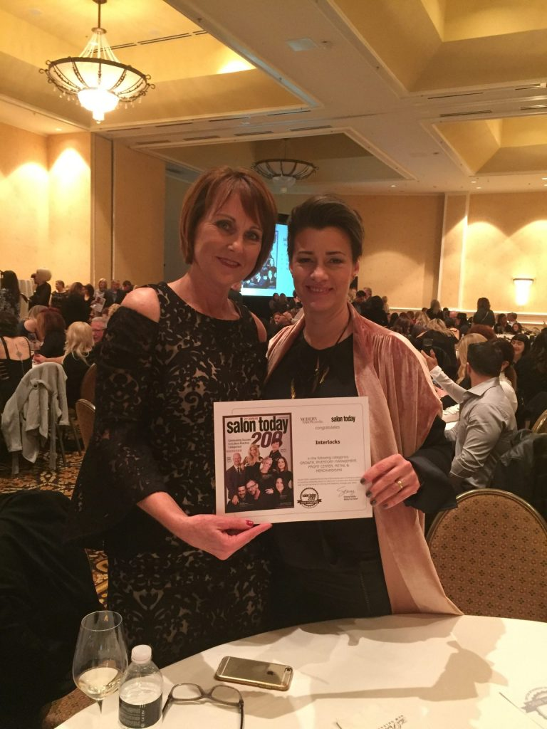 Ginny and Robin holding INTERLOCKS Salon Today 200 award during Serious Business in New Orleans