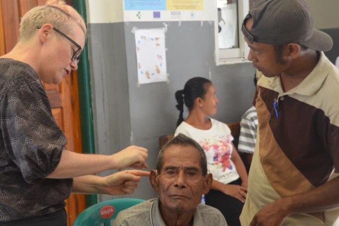 An audiologist adjusts a hearing aid for a patient in Timor Leste.