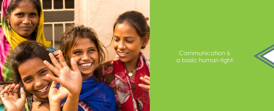"""Three young girls and an older woman in colorful clothing smile and wave at the camera. Text says, """"Communication is a basic human right."""""""