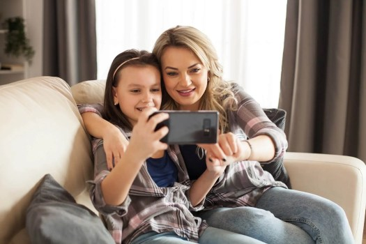 Modern parenting of young mother with her little daughter
