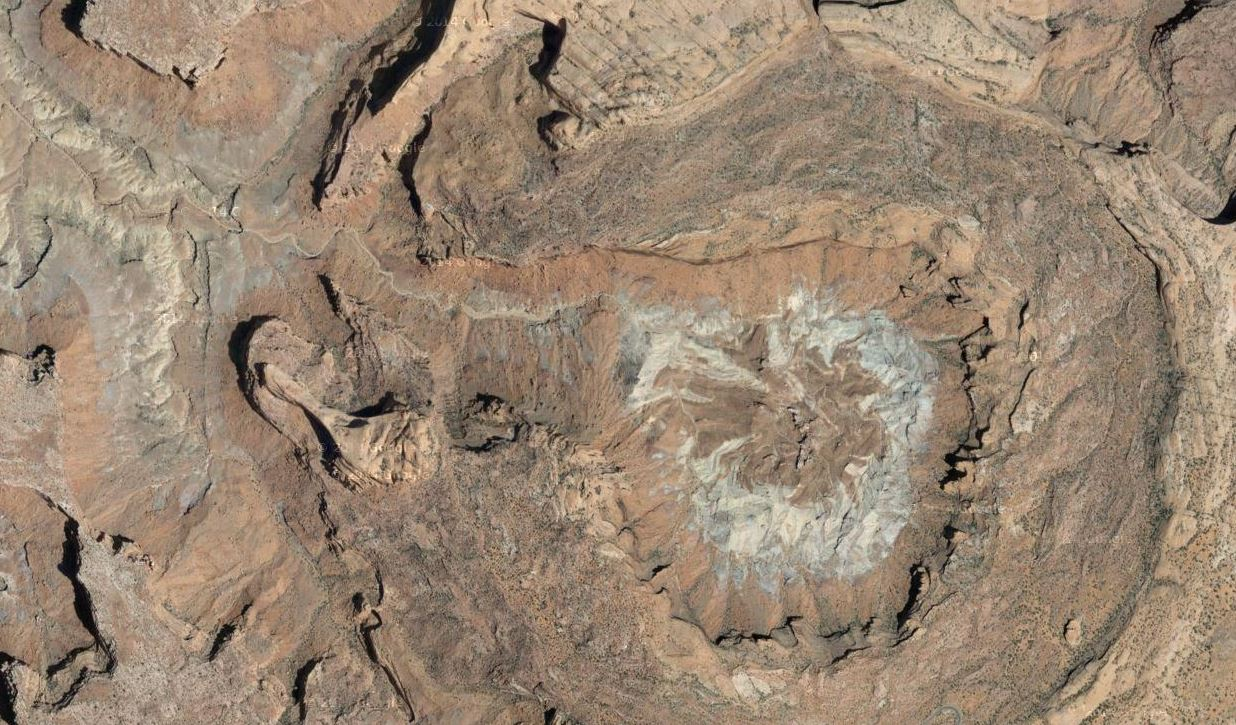 "As seen in this satellite view, the rim of Upheaval Dome is 3 miles across and over 1,000 feet above the core floor. The central peak in the core is 3,000 feet in diameter and rises 750 feet from the floor. Since the late 1990s, the origin of the Upheaval Dome structure has been considered to be either a pinched-off salt dome or a complex meteorite impact crater. In 2007, German scientists reported finding quartz crystals that were ""shocked"" by the high pressure of a meteorite impact. Many geologists now consider the mystery of Upheaval Dome's origin to be solved."