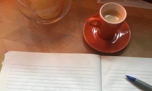 Heft mit Schreiber und Kaffee