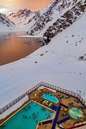 Portillo, Chile : The pool scene as the sunsets behind the Andes at Hotel Portillo.
