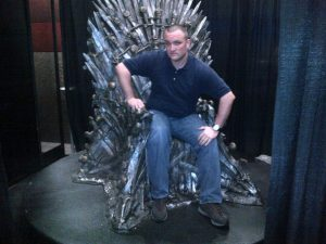 "Ryan Alford sitting on the ""Throne of Swords"" at the 2013 SXSWi."
