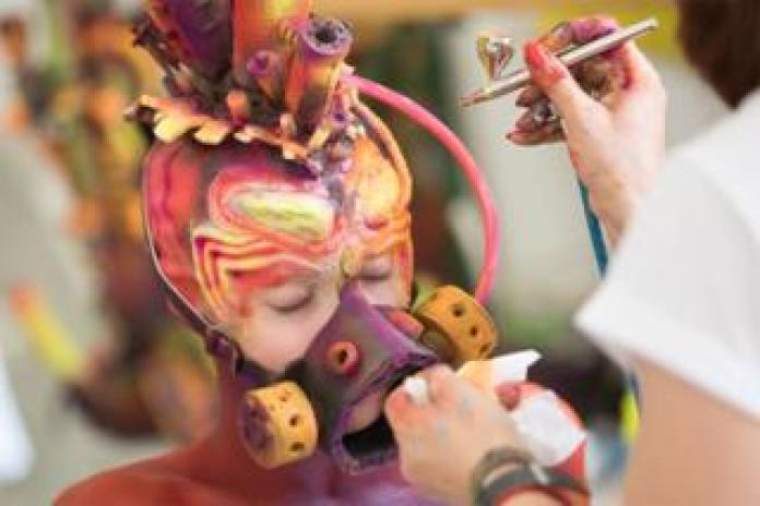 An artist paints a model