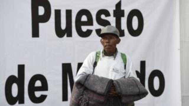A migrant hold blankets as he looks around the stadium in Mexico City where he has sought shelter