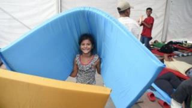 A girl smiles as she carries a mattrass in a stadium-turned-shelter in Mexico City