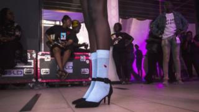 A model in socks and high heels backstage during Dakar Fashion Week in Dakar, Senegal