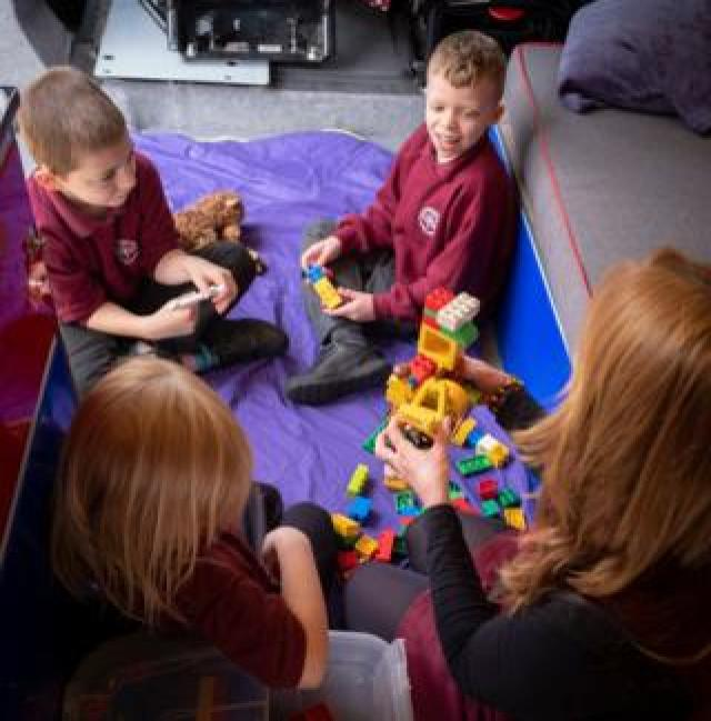 All three children and mentor build a construction out of Lego