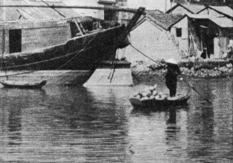 A person punts a boat down a river