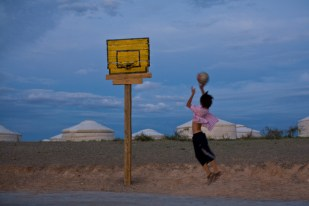 Mongolia, Gobi Desert - Teenage boy playing basketball in the desert.